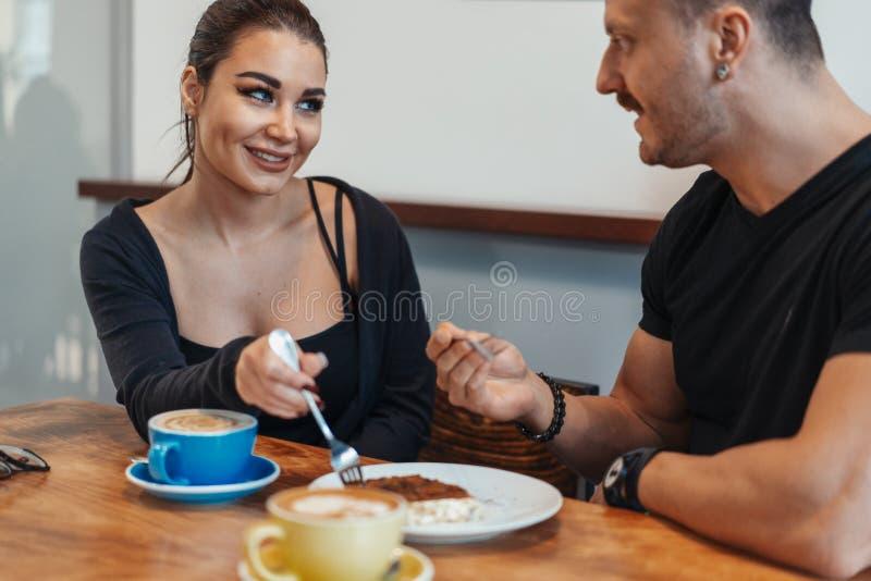 Pares novos que sentam-se no café na data, no café bebendo e comendo a sobremesa foto de stock