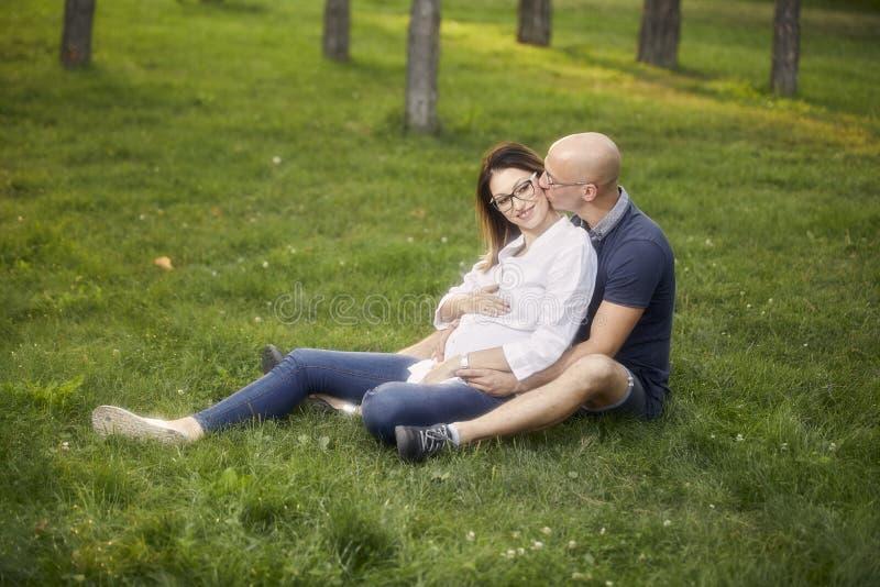 Pares novos que sentam-se no campo de grama no parque sorriso feliz, homem que beija a mulher gravida imagens de stock