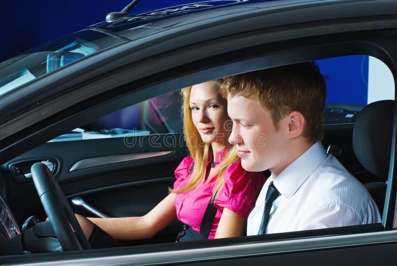 Pares novos que sentam-se no carro fotografia de stock royalty free