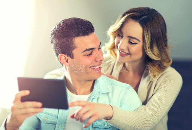 Pares novos que sentam-se no sofá e que olham a tabuleta digital imagens de stock royalty free