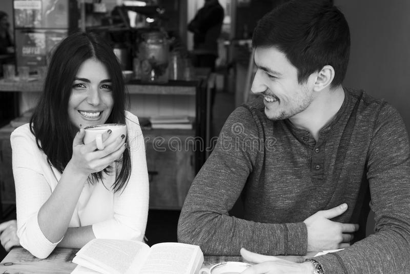 Pares novos que sorriem na cafetaria foto de stock