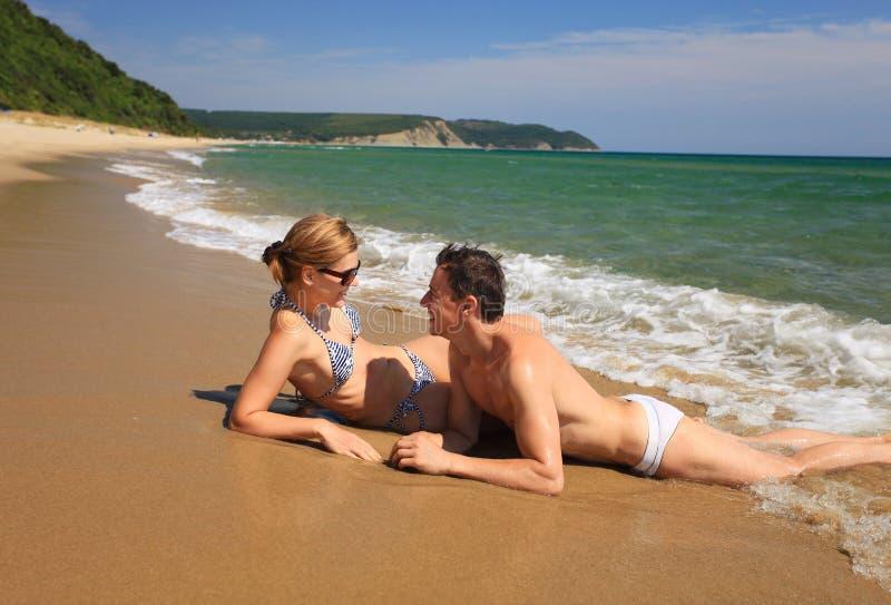 Pares novos que sunbathing na praia foto de stock
