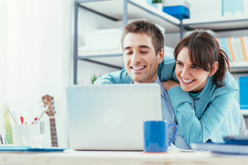 Pares novos que surfam a Web em casa imagem de stock royalty free