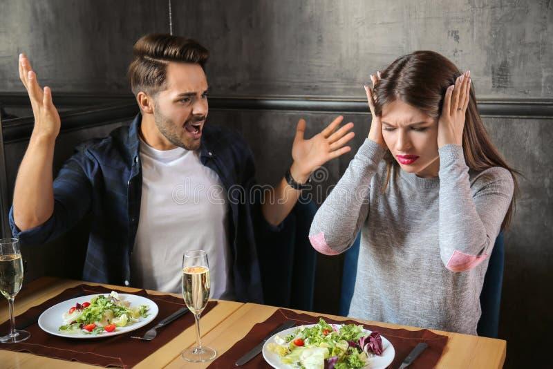 Pares novos que têm argumentos na data no restaurante foto de stock royalty free