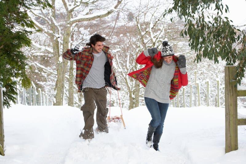Pares novos que têm a luta do snowball foto de stock