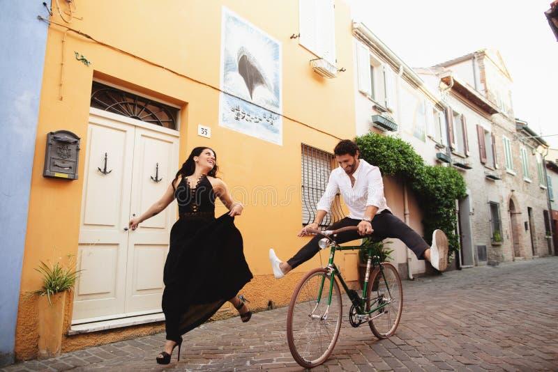 Pares novos que têm o divertimento ao dar um ciclo História de amor na cidade velha de Itália foto de stock
