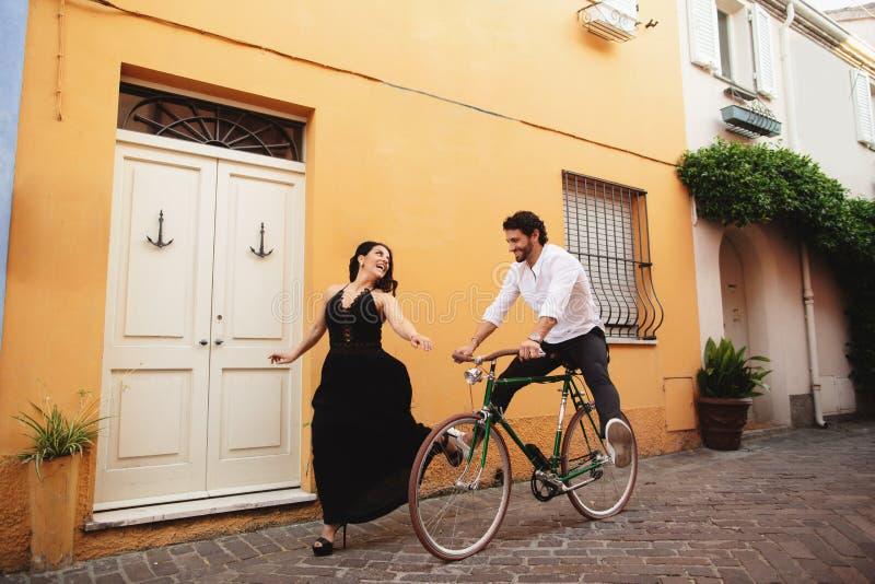 Pares novos que têm o divertimento ao dar um ciclo História de amor na cidade velha de Itália imagens de stock royalty free