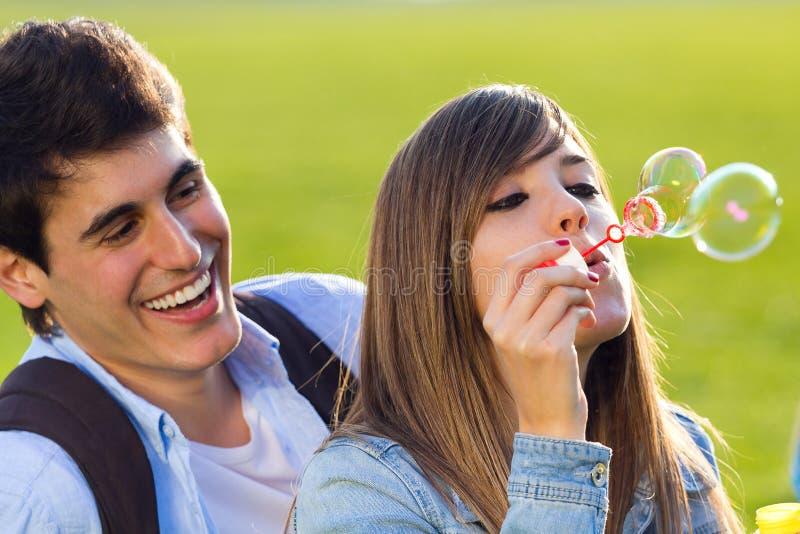 Pares novos que têm o divertimento com bolhas de sabão no parque imagens de stock