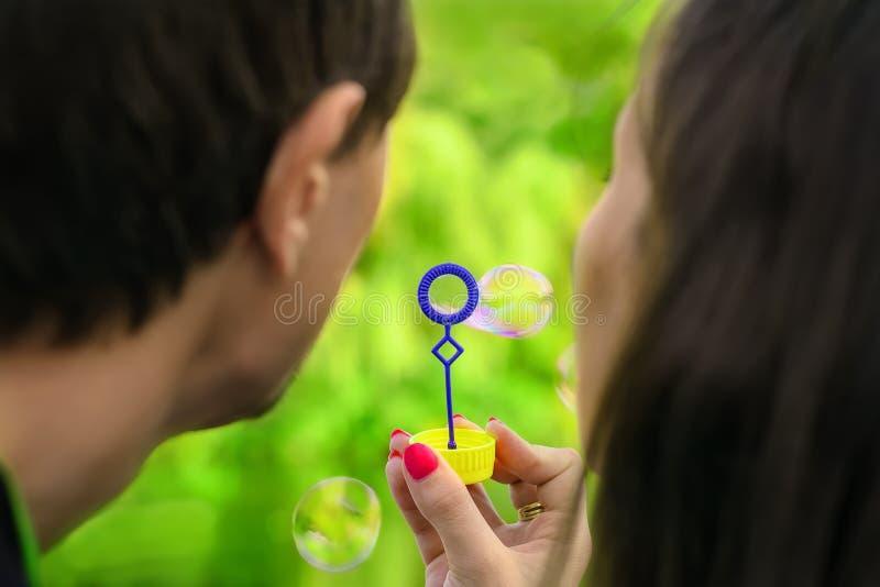Pares novos que têm o divertimento com bolhas de sabão no parque imagens de stock royalty free