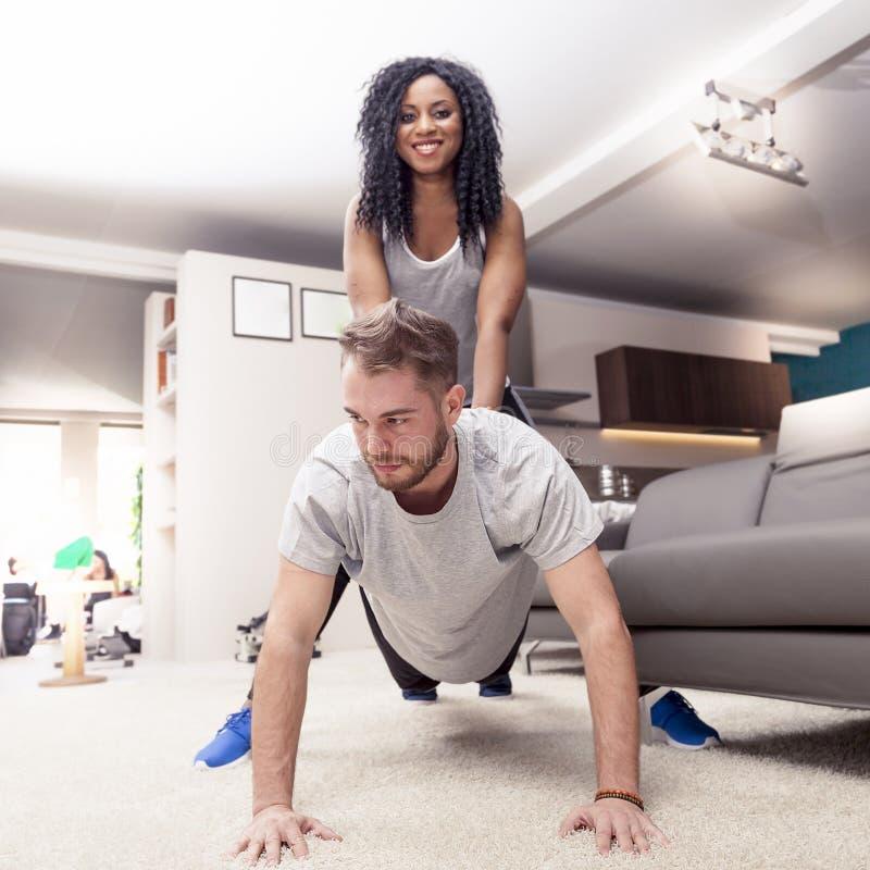 Pares novos que têm o divertimento que faz a ginástica em casa imagens de stock royalty free