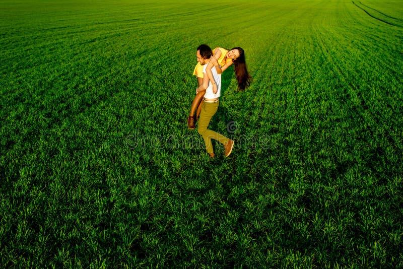 Pares novos que têm o divertimento no campo verde na primavera ou no summ fotografia de stock