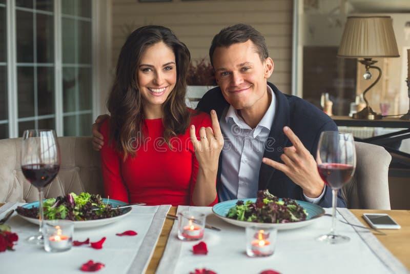 Pares novos que têm o jantar romântico no restaurante que senta-se junto tomando o grimase das fotos foto de stock
