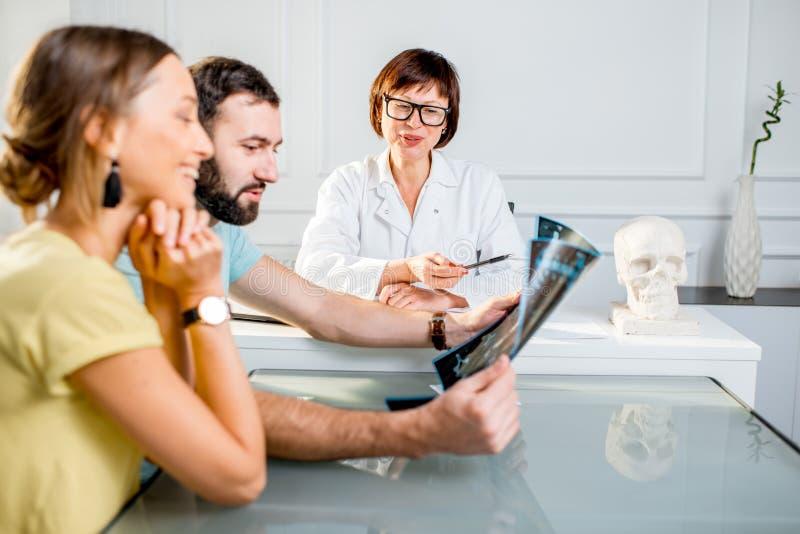 Pares novos que têm uma consulta com doutor superior imagem de stock