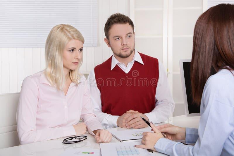 Pares novos que têm uma nomeação no banco ou no seguro. imagem de stock royalty free