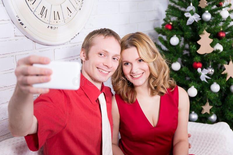 Pares novos que tomam a foto do selfie na frente da árvore de Natal imagens de stock royalty free