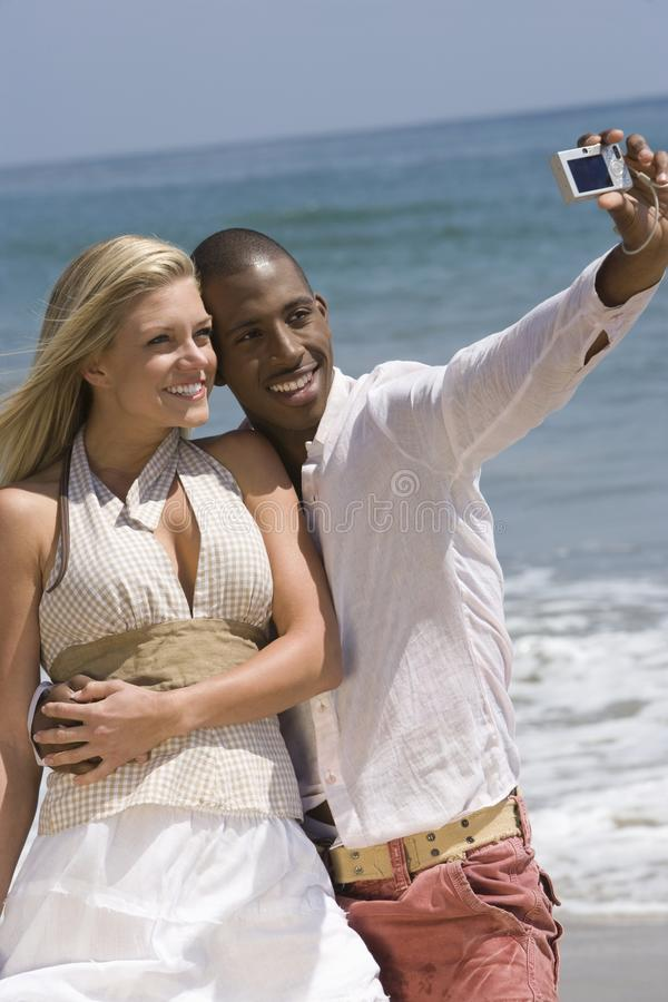 Pares novos que tomam a fotografia do autorretrato na praia imagens de stock royalty free