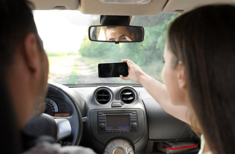 Pares novos que tomam o selfie no carro na viagem por estrada fotos de stock
