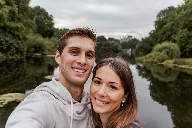 Pares novos que tomam um selfie no parque em Londres fotografia de stock