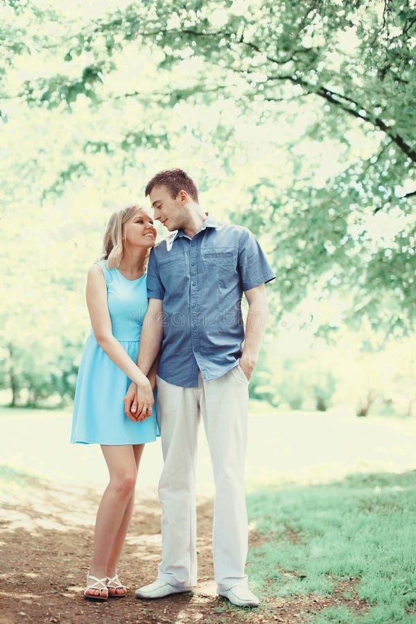 Pares novos românticos felizes no amor que anda junto na mola fotos de stock
