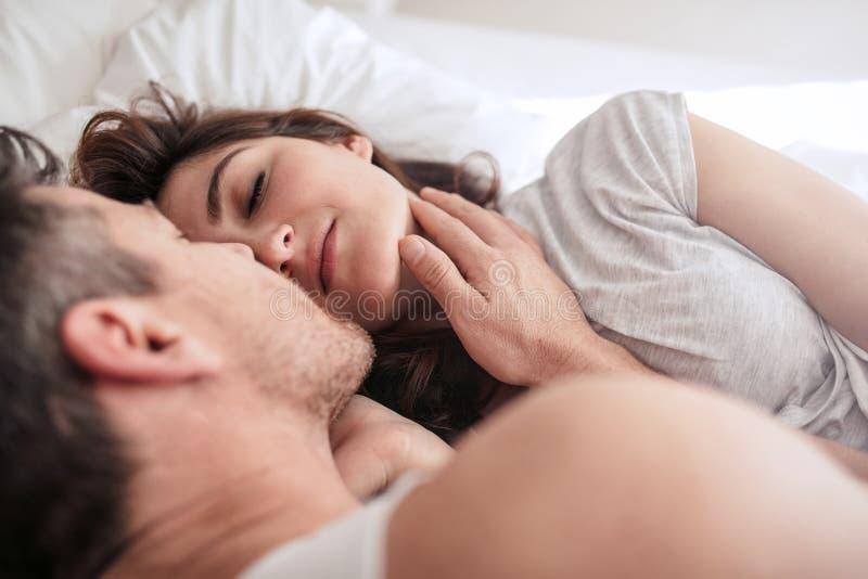 Pares novos românticos na cama fotografia de stock royalty free