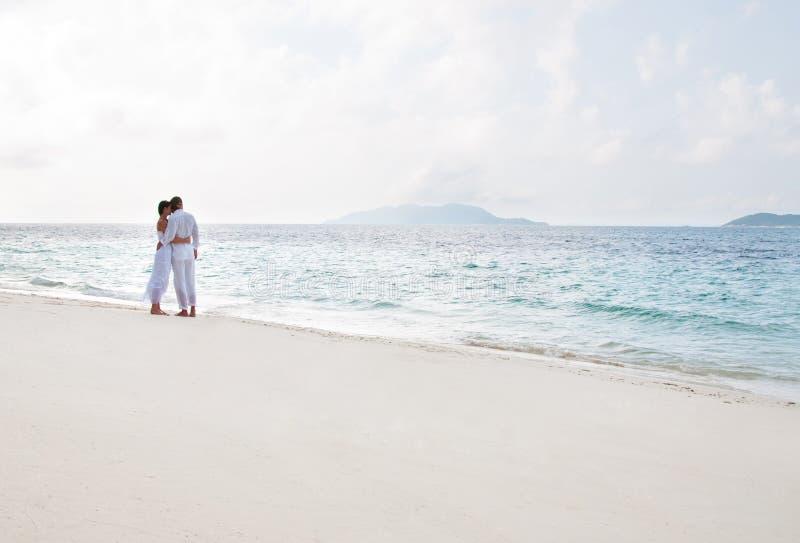 Pares novos românticos na costa de mar imagens de stock