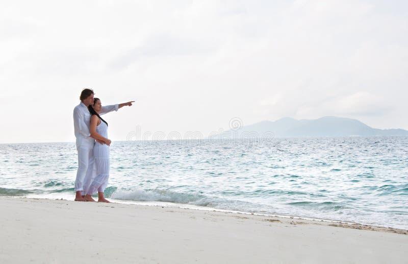 Pares novos românticos na costa de mar fotografia de stock royalty free