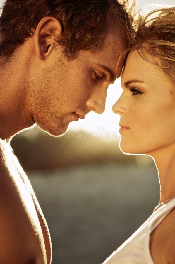 Pares novos românticos na praia imagens de stock