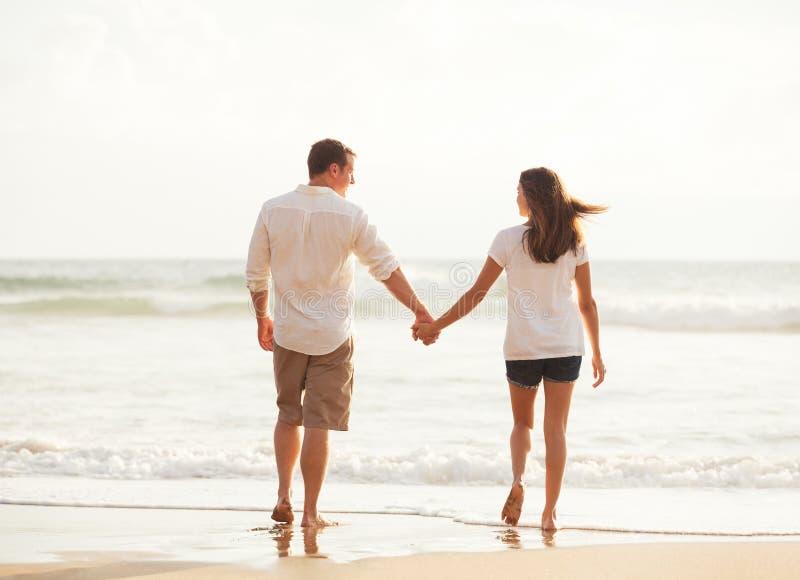 Pares novos românticos na praia no por do sol fotografia de stock royalty free