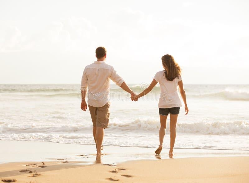 Pares novos românticos na praia no por do sol imagens de stock royalty free