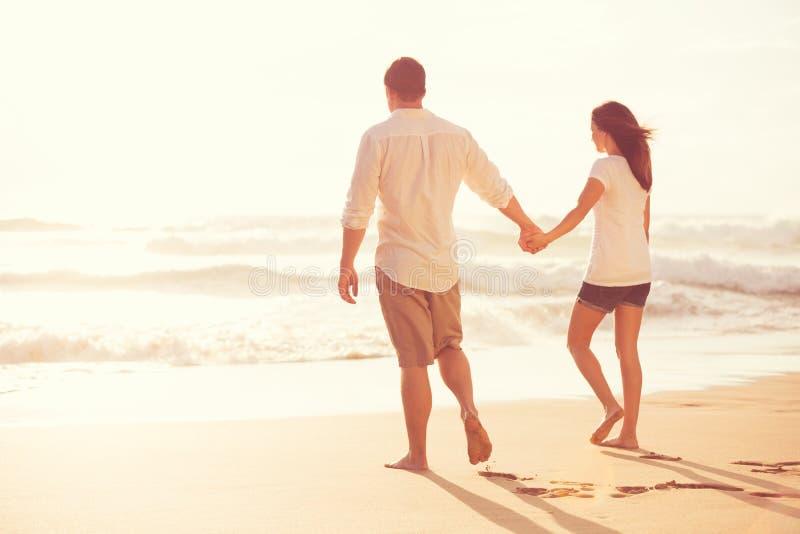 Pares novos românticos na praia no por do sol fotografia de stock