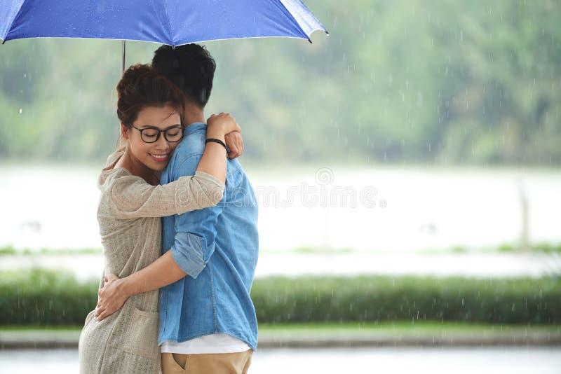 Pares novos românticos que abraçam na chuva fotografia de stock