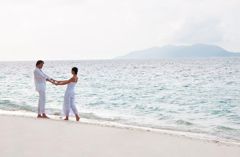 Pares novos românticos que andam na costa de mar fotografia de stock
