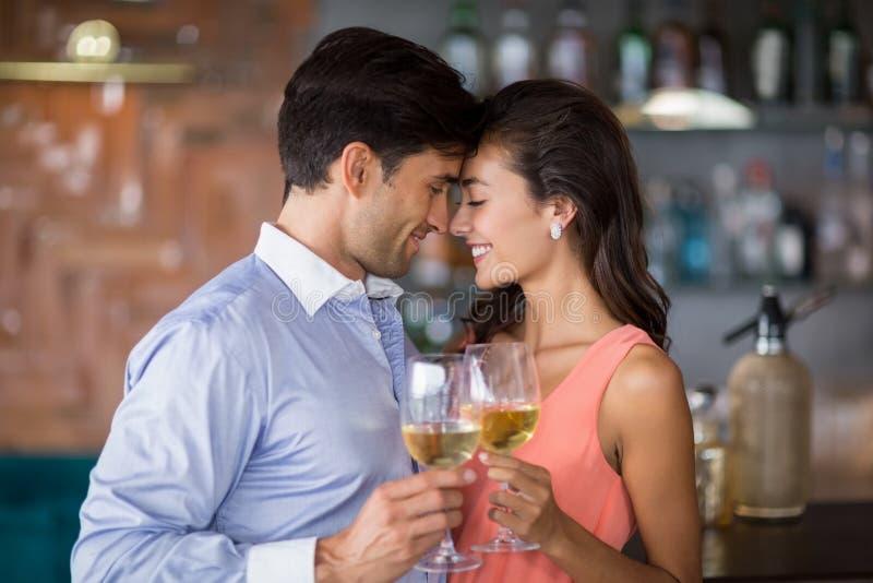 Pares novos românticos que brindam vidros de vinho fotos de stock
