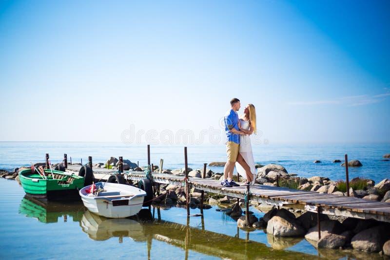 Pares novos românticos que estão no cais foto de stock