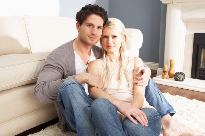 Pares novos românticos que relaxam junto em casa imagem de stock royalty free