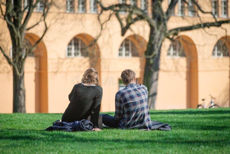 Pares novos românticos que sentam-se na grama e que relaxam no centro da cidade Ocasional, conceito do estilo de vida fotografia de stock royalty free