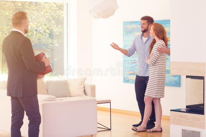 Pares novos satisfeitos com o apartamento imagens de stock