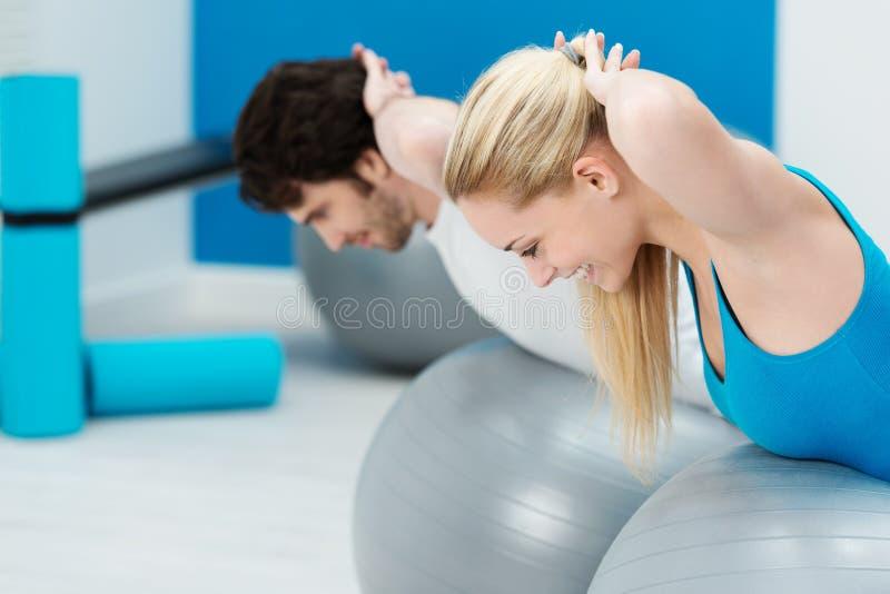 Pares novos saudáveis que fazem exercícios de Pilates fotos de stock