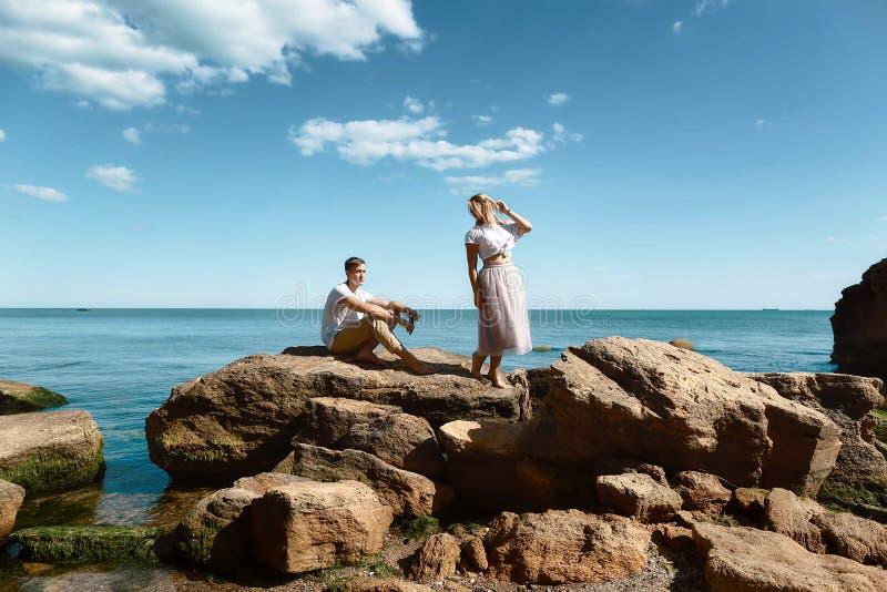 Pares novos sensuais no amor que está na rocha no mar perto da praia com penhascos grandes Homem e mulher que olham em se, imagem de stock royalty free