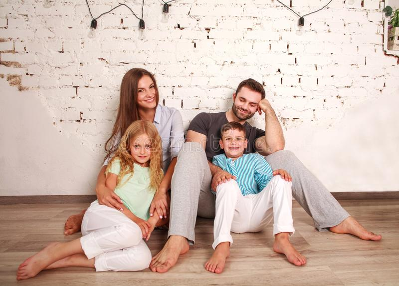 Pares novos sonhadores felizes de pais com suas duas crianças em casa junto fotos de stock