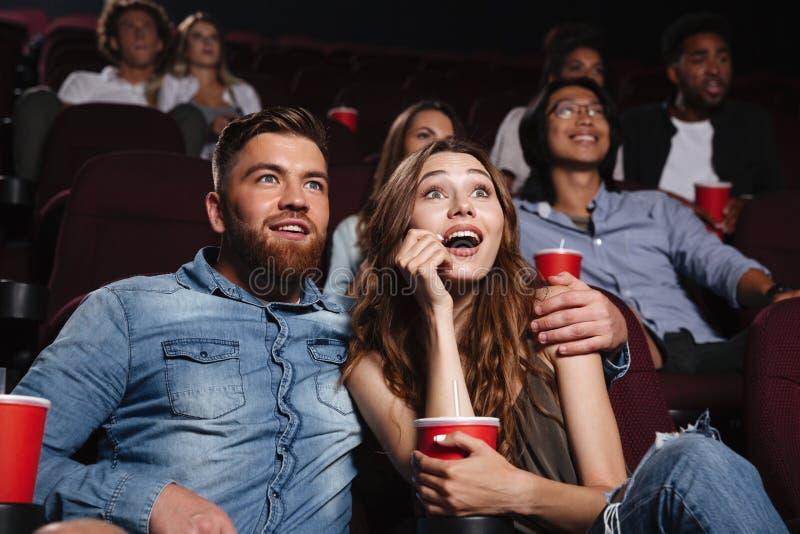 Pares novos surpreendidos que sentam-se no cinema foto de stock