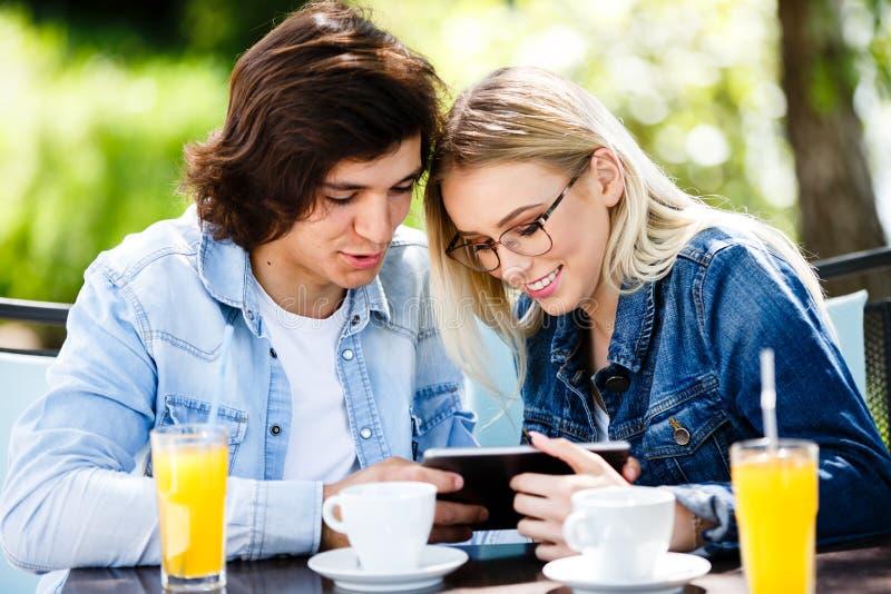 Pares novos usando a tabuleta ao sentar-se junto no café fotografia de stock royalty free