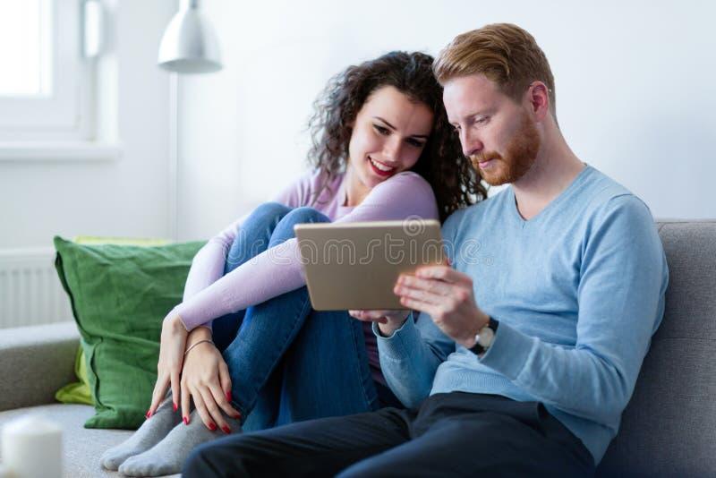 Pares novos usando a tabuleta digital em casa imagem de stock