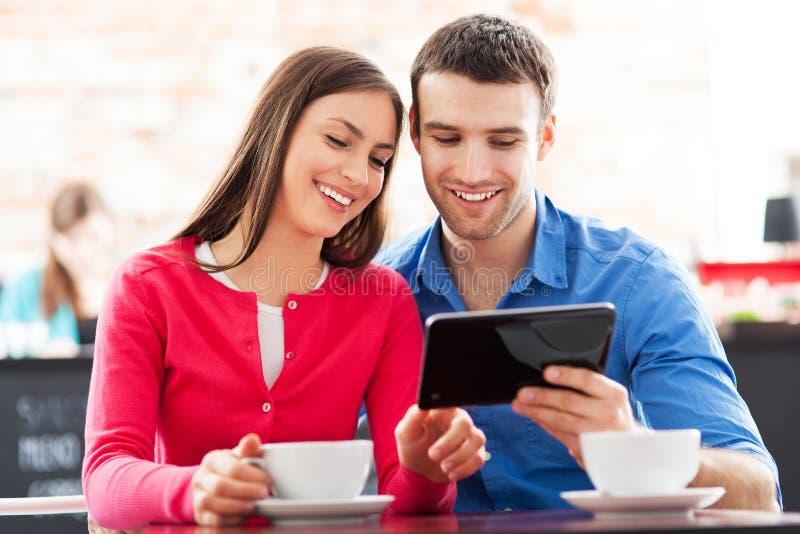 Pares usando a tabuleta digital no café fotos de stock royalty free