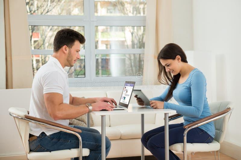 Pares novos usando a tabuleta e o portátil digitais fotos de stock royalty free