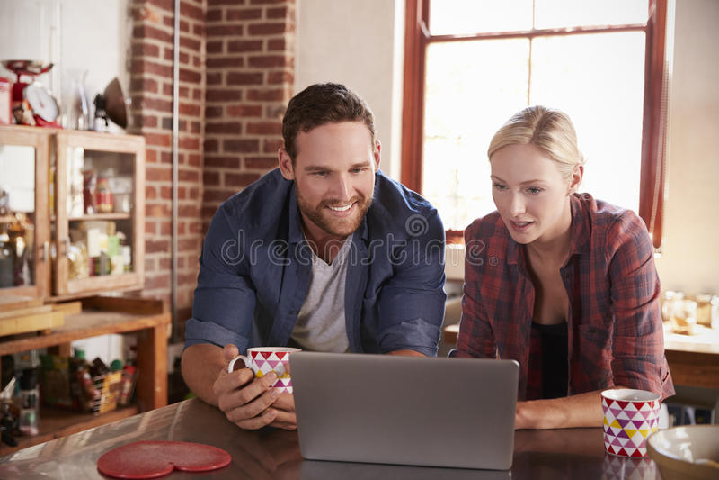 Pares novos usando um portátil na cozinha, fim acima, vista dianteira foto de stock