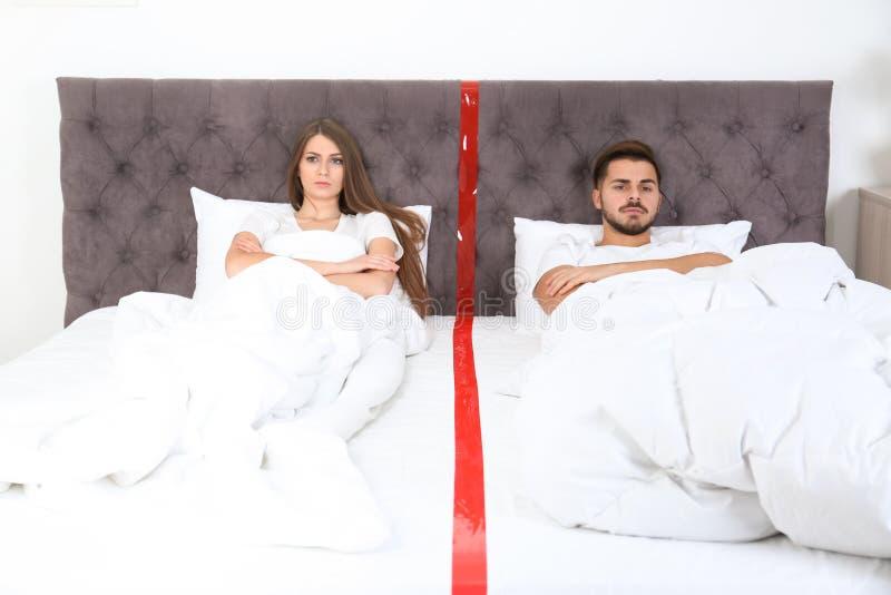 Pares novos virados com os problemas do relacionamento que encontram-se separadamente na cama foto de stock