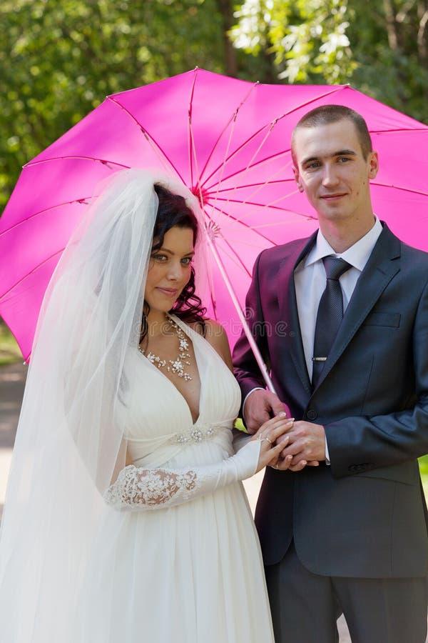 pares Nuevo-casados bajo un paraguas rosado foto de archivo libre de regalías