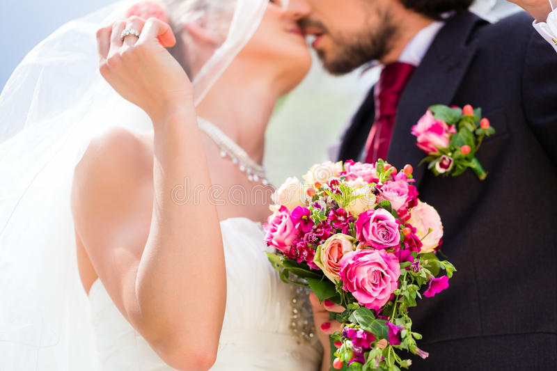 Pares nupciais que beijam sob o véu no casamento fotos de stock royalty free