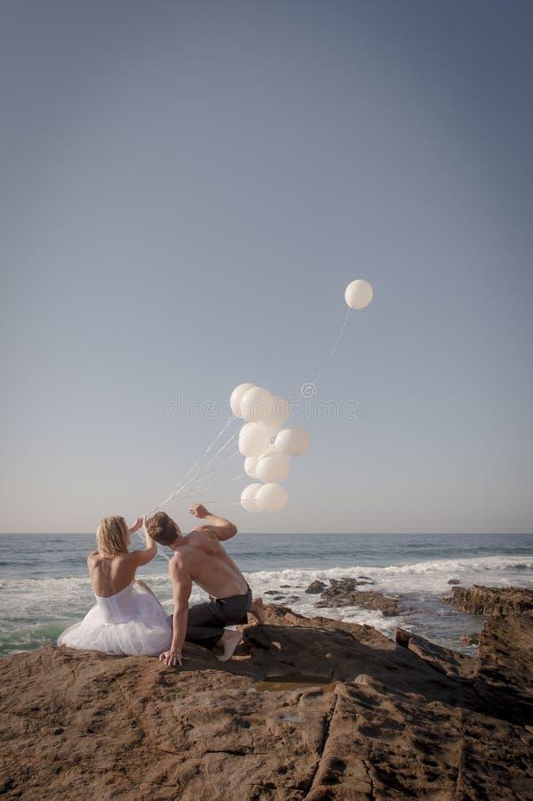 Pares nupciales hermosos jovenes que lanzan los globos blancos en la playa fotografía de archivo